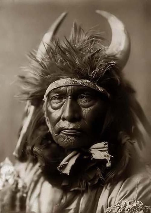 Bull Chief, an Indian Warrior. It was made in 1908 by Edward S. Curtis.The illustration documents this Indian in a head-and-shoulders portrait, facing front. He is wearing a buffalo headdress with horns.