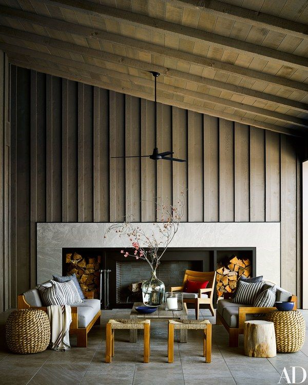 Rustic furnishings mingle before the fireplace of a covered terrace | archdigest.com