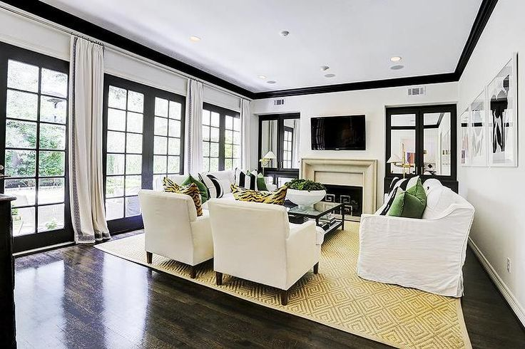Black And White Living Room Features White Walls Accented With Black Crown  Moldings Fitted With A Row Of Black French Doors Dressed In White Curtains.