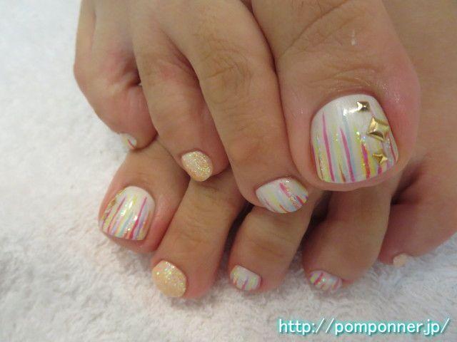 カラフルアートがポップなフットネイルColorful Art is foot nail pop. The monochromatic painted off-white, I put a line from the tip to the colorful. The plus lame, I put the studs decoration.
