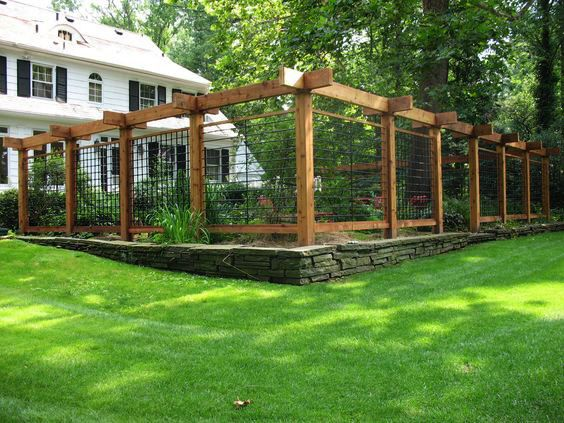 The old stone garden fence was kept in place as a newer, bigger one was built on top of it. The affect gives this garden a cool, eclectic style with the uneven footing of the stones and the beefy wooden beams that support the tall structure.