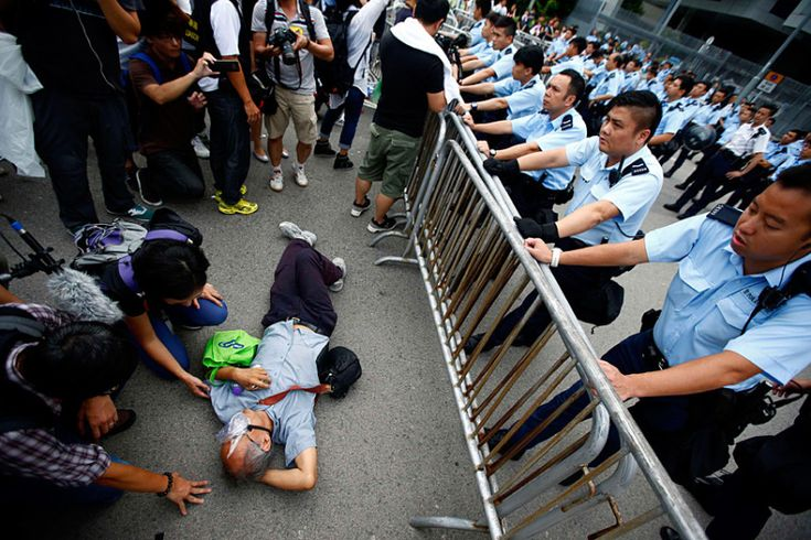 An elderly protester is urged by policemen to stand up and clear the office's entrance of Hong Kong's Chief Executive Leung Chun-ying on the fifth day of the mass civil disobedience campaign Occupy Hong Kong