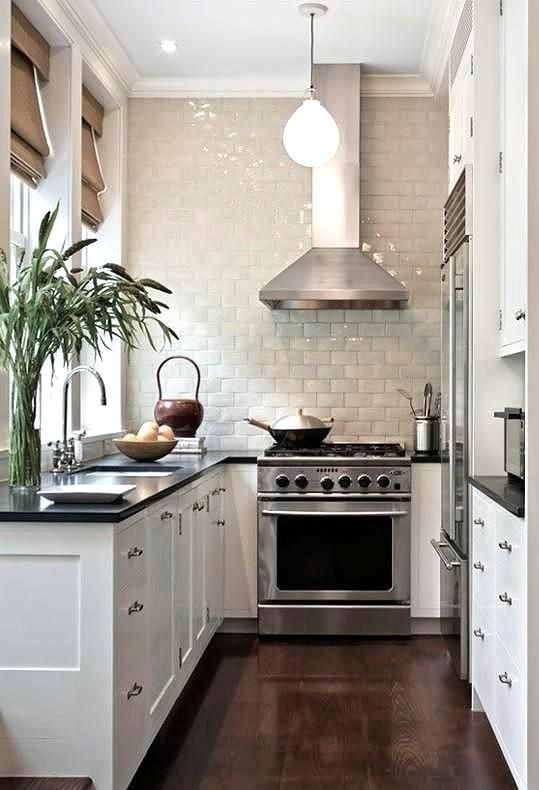 Narrow Black And White Kitchen With Hardwood Floors, Silver Accents And  Bright White Subway Tiles