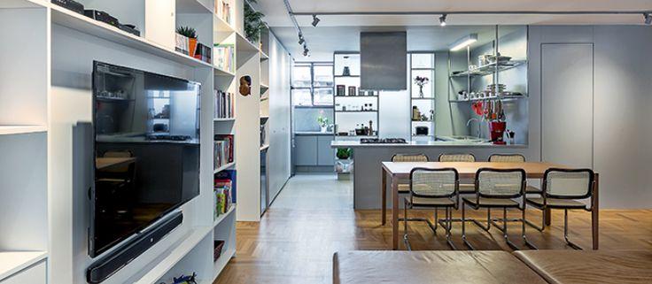 A divisória de marcenaria com vidro comum (6 mm) e película jateada deixa a claridade da área de serviço entrar, mantendo a privacidade. A cozinha foi toda tingida de cinza: porcelanato no piso, laminado nas paredes (e na porta do lavabo) e tinta no teto. Repare na prateleira de inox, desenho dos arquitetos, sobre a pia. | <i>Crédito: Foto: Haruo Mikami