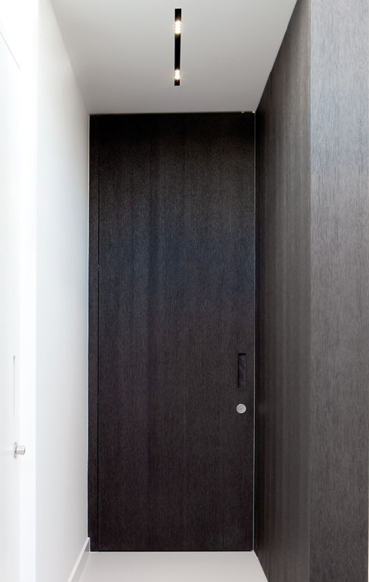 Dark wooden doors and integrated lighting, interior design by Wilfra.