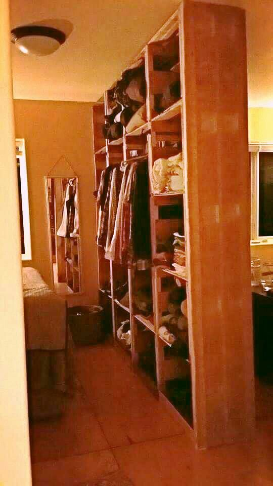 """Room divider and clothing storage made out of """"chinacrates"""" Covered with burlap."""