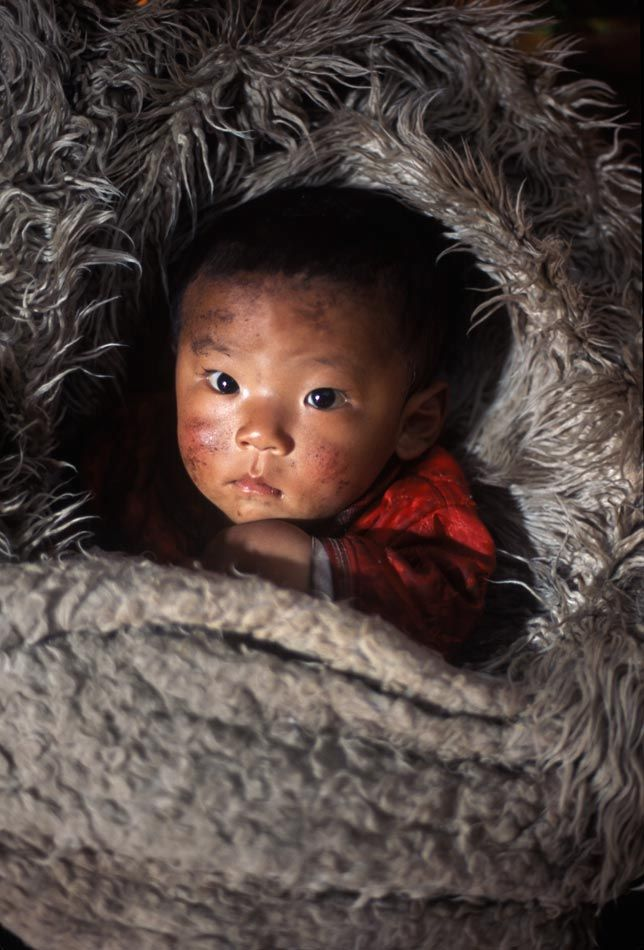 A tibetan child wrapped in Yak fur. Photo Credit: Alison Wright