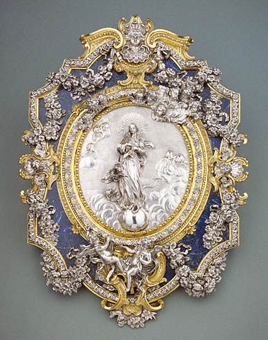 """1730-1740 Italian (Sicily).""""Surrounded by the deep blue, lapis lazuli background of the gold frame, the silver Virgin Mary, crowned as Queen of Heaven, projects from the background in an elegant swirl of drapery. She stands on a globe, symbol of her dominion with Christ....Under her feet she tramples a snake, understood as a sign of the Immaculate Conception."""""""