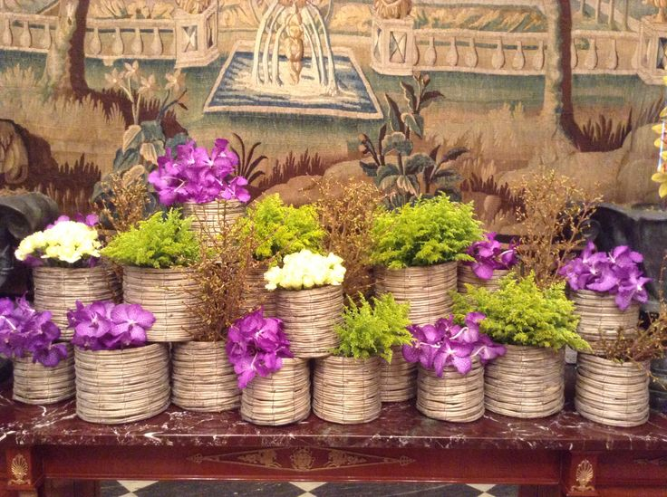 Mixed flowers and greenery in natural material vases