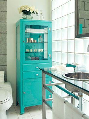 Sleek and modern with its stainless steel and glass top vanity, glass block window and all white tile. But I have to tell you my favorite part of this is that awesome turquoise cabinet. It makes the room in my opinion.