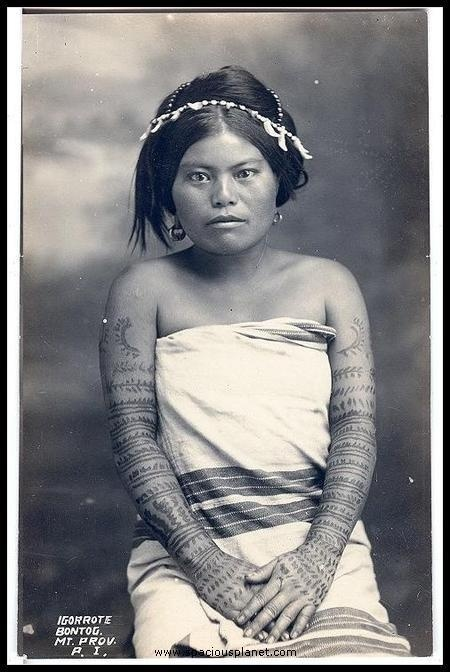 A young woman from Bontoc in the Philippines showing her traditional tattoos. (1904)