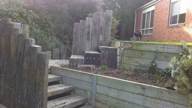 I wanted access to the lower terrace of the yard, and decided on railway sleepers. Love the silver grey with flecks of rust. We painted the retaining walls dark grey. Love it!
