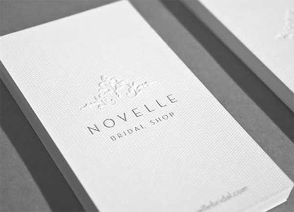 minimal bridal shop business card with embossed logo in elegant white
