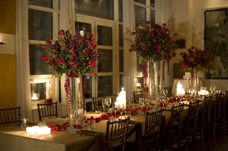 A tall centerpiece featuring red mokara orchids burgundy
