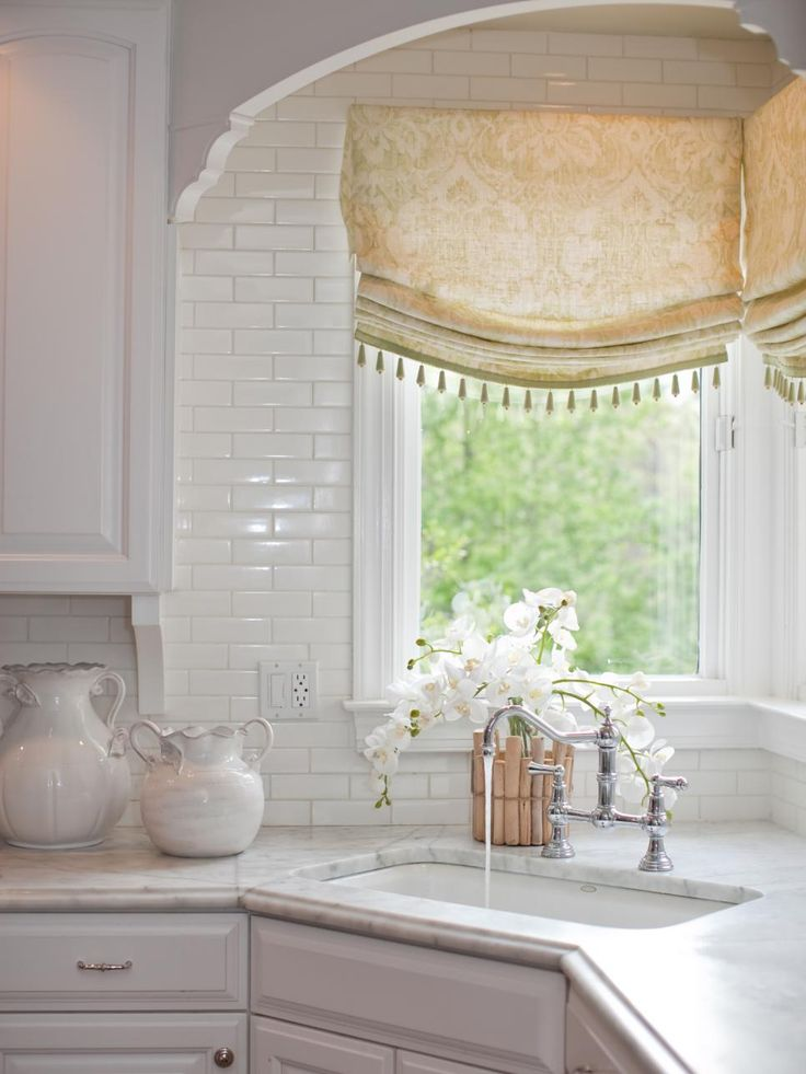 a corner sink takes center stage in this white traditional kitchen beaded roman shades add