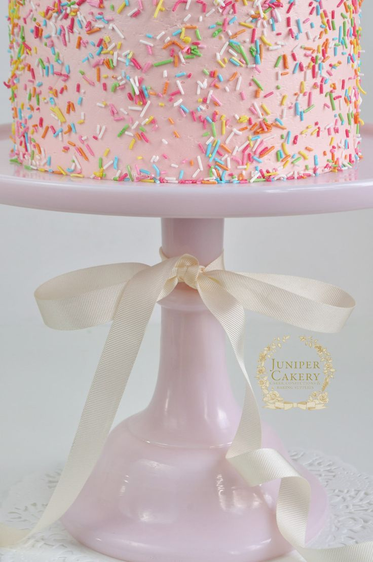 Rainbow sprinkles on a pink cake by Juniper Cakery