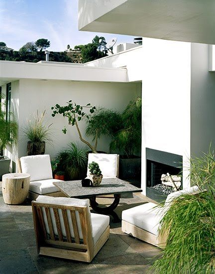 Mid Century Modern outdoor seating area. Love the fireplace and the potted plants. There's a stark yet inviting feel to this. Kind of futuristic