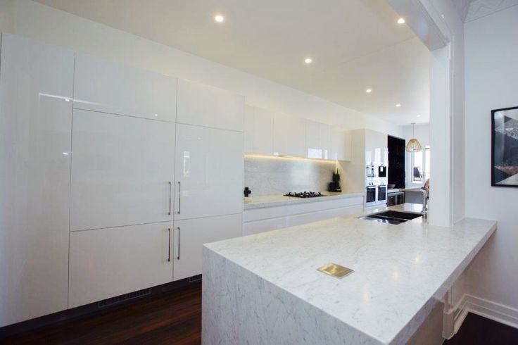 Bianco Carrara marble kitchen tops and spkashback, 2 PAC polar white cabinetry with fully integrated refrigerators.