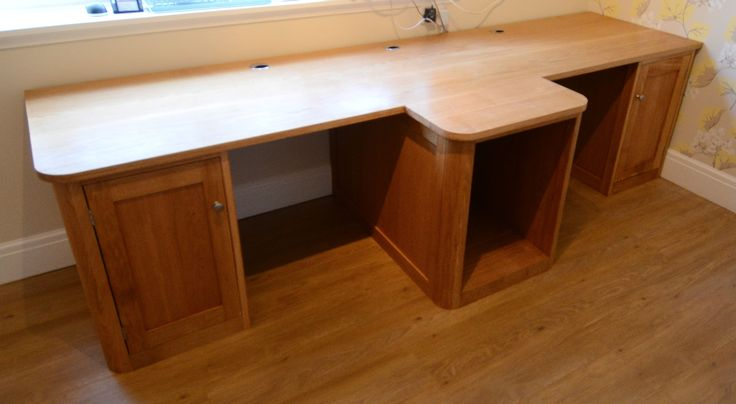 Oak double workstation desk -   A bespoke solid oak desk, designed to be used by two people.  Each person having their own storage cupboard.  A curved open backed (for ventilation) central unit allowing for storage of PC towers, cables & other computer accessories.  The worktop was made with full staves of 34mm solid prime grade european oak.  High quality cable tidys were inserted into the top for easy cable management.  Made for a customer in Upton-by-Chester.