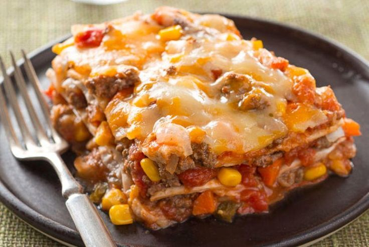 """""""This is The Best Layered Burrito Bake you'll ever try. It has ground beef, salsa, refried beans, and cheese that are layered between tortillas. This is definitely a burrito bake that's like a fiesta in a dish."""""""