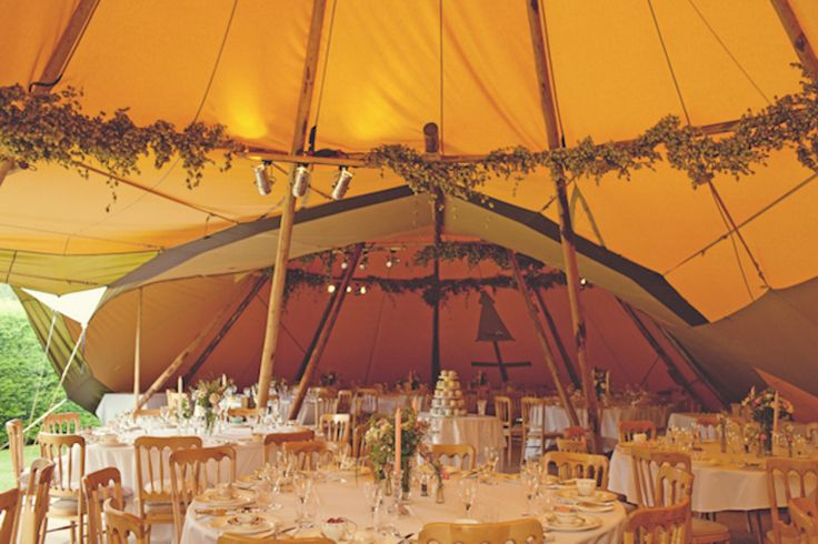 amber-colored tent with wooden poles and vines for a boho wedding