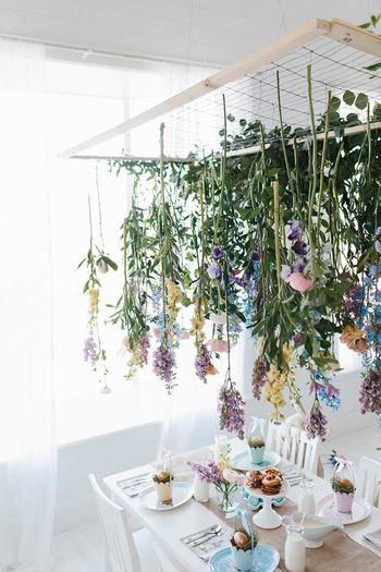 フラワーインスタレーションをインテリアに取り入れた斬新な食卓風景です。 網をはった木枠を天井に吊るし、お花をワイヤーでくくりつけています。