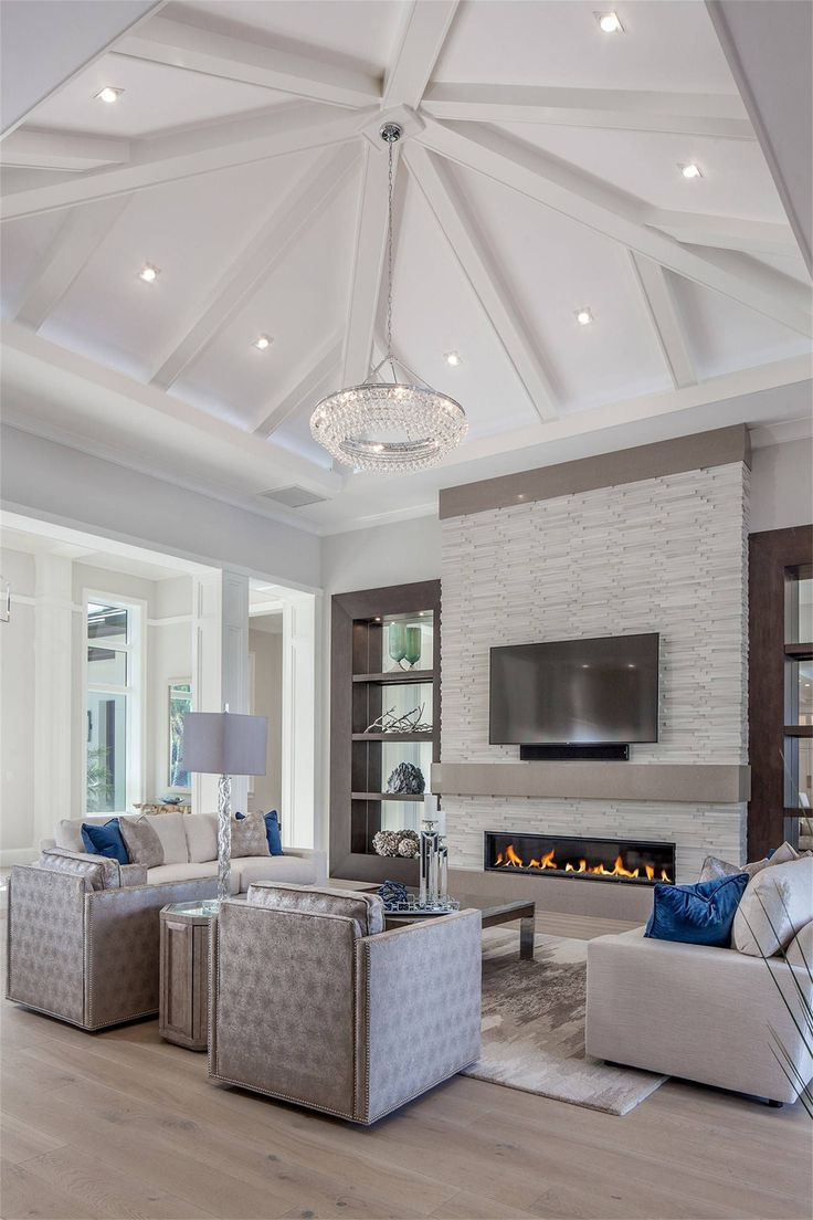 727 Buttonbush Lane, Naples, FL 34108 | Coastal contemporary living room with white ceiling beams, fireplace and wall of stone. By Imperial Homes of Naples. Pelican Bay #coastallivingroomsfireplace