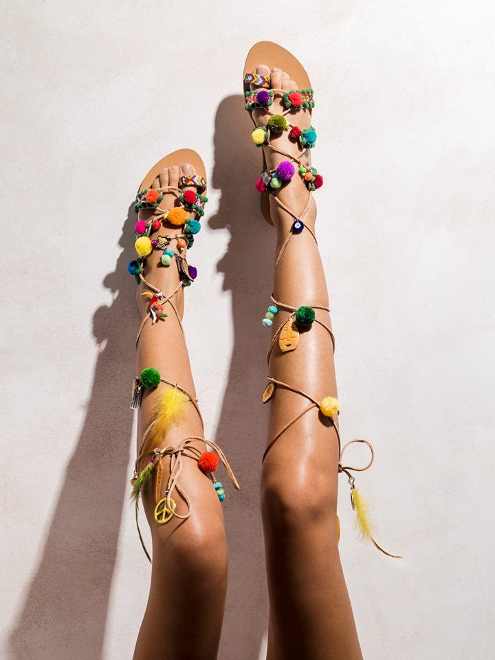 Marabu  Multi-colored macramé friendships, pom poms, hand-painted jungle themed metal charms, feathers, bone pendants.   Get the experience: http://www.elinalinardaki.com/shoes/sandals/new-collection/sandal-marabu/