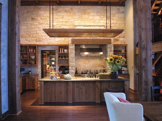 Rustic Kitchen: Limestone walls make this rustic kitchen one of a kind. Open wooden cabinets provide a casual feel, while state-of-the-art appliances add a touch of sleek modernity. Suspended lighting over the center island gives a significant architectural statement. From HGTVRemodels.com