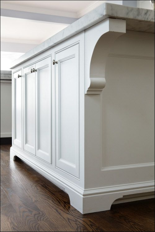 Simple yet elegant handcrafted corbels on the island. Scrolled toe is constructed with our F-39 moulding for a beautiful furniture style look. Inset Cabinetry. White kitchen in Milwaukee, WI by A. Fillinger Inc.
