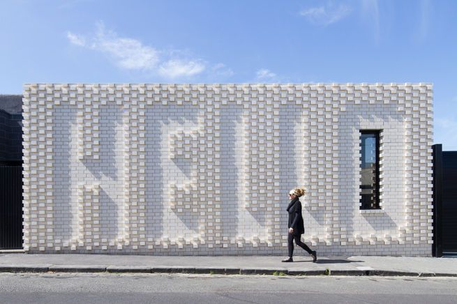 "This Victorian-era home in Melbourne, renovated by OOF! Architecture, maintains privacy from the street, but does so in an unusually ""friendly"" manner—with a giant brick wall that spells out ""Hello,"" a collaboration with local artist Rose Nolan. The residents wanted their house to appeal to passersby, since it sits on a well-trafficked block near a café.  Photo by: Nic Granleese"