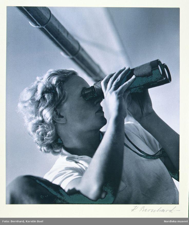 Kvinna med kikare. Ung kvinna med kort, blond, lockig frisyr klädd i kortärmad sporttröja ombord på båt, tittar i kikare. Fotograf: Kerstin Bernhard