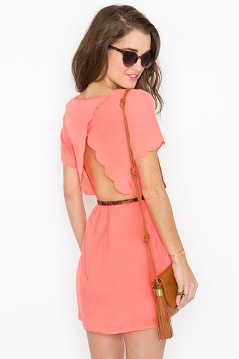 coral dress featuring scalloped detailing at sleeve and cutout back. Scoop neckline, stretch panel at back. Partially lined
