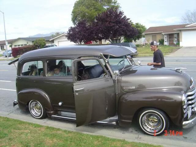 Lowrider early Chevy Suburban of the 1947 1948 1949 1950 1951 variety with a sweet visor, chrome running boards, and the rare clam shell rear doors topped off with Spotlights.