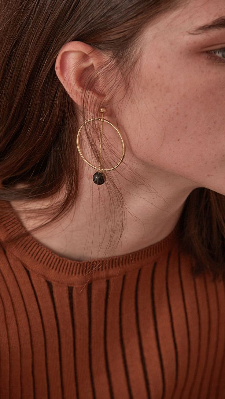 Kael Earring, a set of circle earrings with black marble-look ball drops. COMPOSITION AND CARE Gold plating can be subject to tarnishing. This is a natural oxidization process which occurs when metal