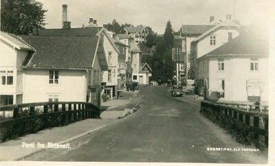 EIDSVOLL. Nært gateprospekt fra bro. Butikker og bil. Brukt.Årstall:1929