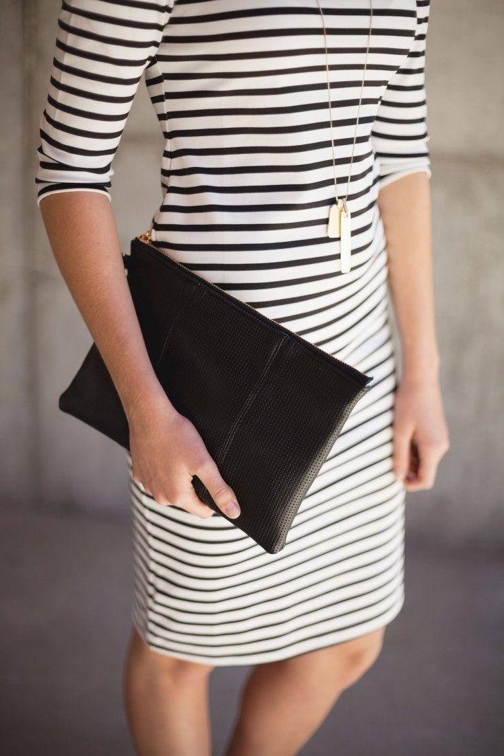 This perforated black clutch is perfect for taking any outfit from day to night.