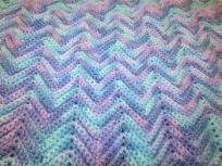 """Variegated light Aqua, medium blue and blue.  """"Ripple"""" stitch. 100% Acrylic yarn.  Large """"Lap"""" Afghan or small cover-up.  61"""" long x 31"""" wide.  Machine washable on gentle cycle, cold/warm water. Dry on low heat. Do not hang to dry--this causes stre..."""