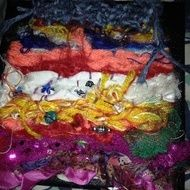 Various yarns ribbons and fabrics woven on loom embellished with beads and sequins hand stitched onto canvas