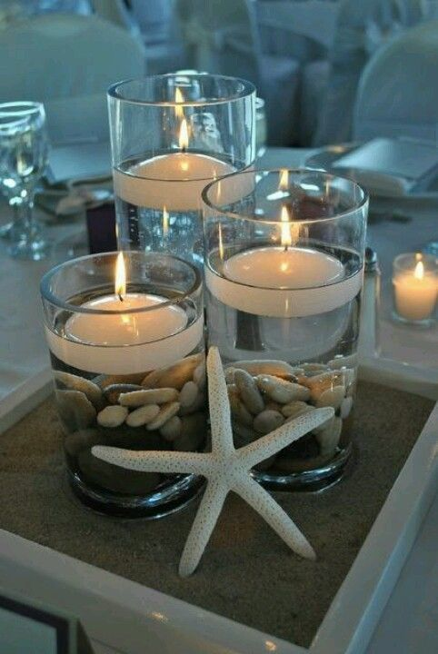 Beach Wedding Centerpiece: Life is a beach when you love by the sea! Celebrate your seaside wedding with beach inspired layers of sand, shells, and sea creatures. Floating votives enhance the romance and protect the flame from an ocean breeze.