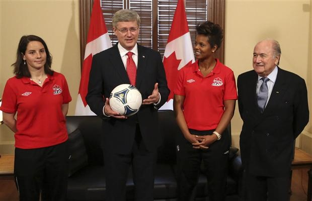 Canadian Prime Minister Stephen Harper poses for a photo with Canada's women's team defender Rhian Wilkinson (L), goalkeeper Karina Leblanc (2nd R) and FIFA President Sepp Blatter in Harper's office in Ottawa, May 4, 2012, to promote the FIFA Women's World Cup soccer tournament which will take place in Canada in 2015.