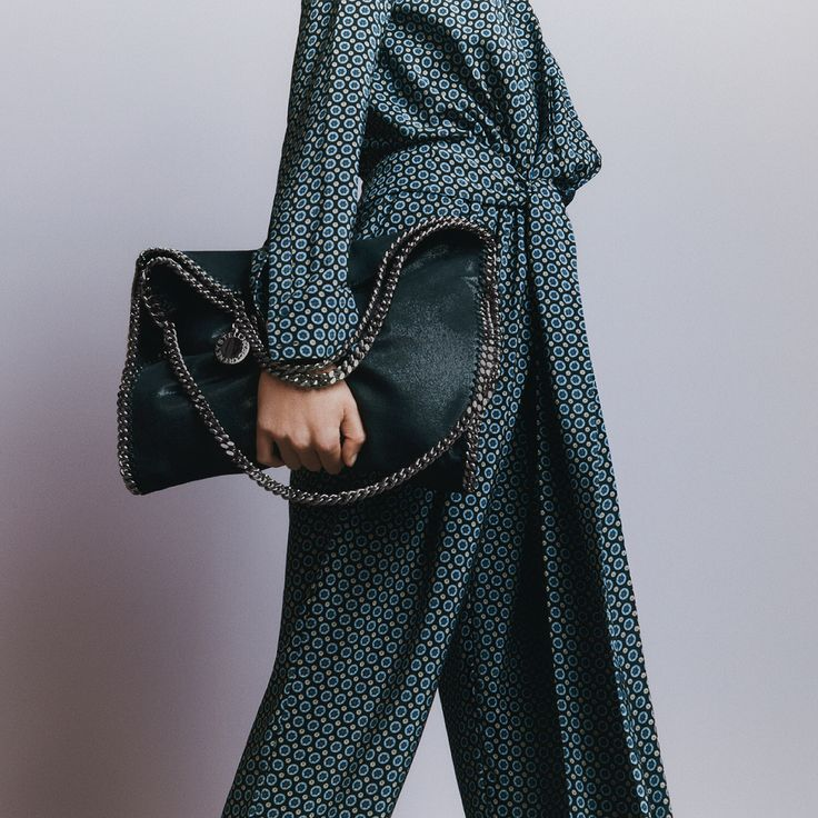 All tied up. Take it from day to evening in printed jumpsuits inspired by vintage men's ties styled with our iconic cruelty-free #Falabella bag in teal.