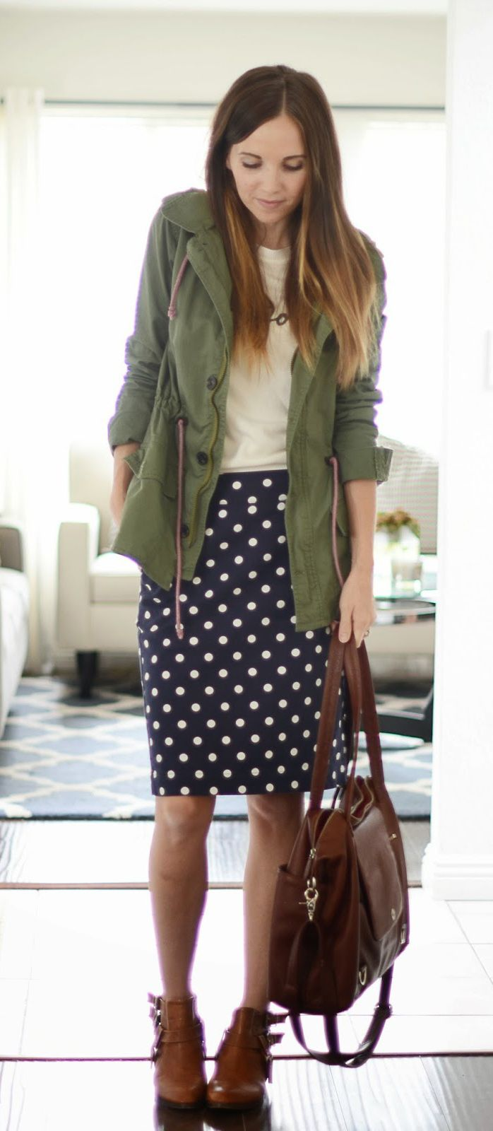 white top over polka dot dress with olive button down and studded boots