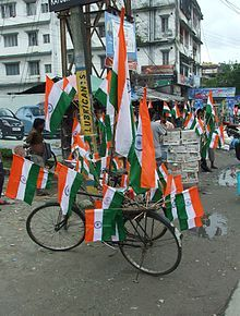 Several flags mounted on a bicycle parked on a road for India's Independence Day usually celebrated on August 15th.