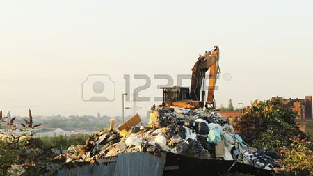 Junk yard digger on a mound of refuse with two magpies sitting a top the arm