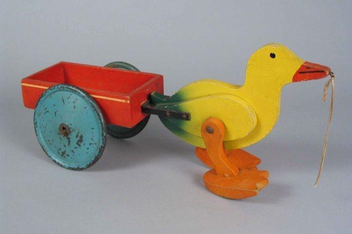 Houten loopeend met kar, gele eend met grote oranje poten die gaan lopen bij voorttrekken, rode laadbak op grote blauwe metalen wielen - Museum Rotterdam