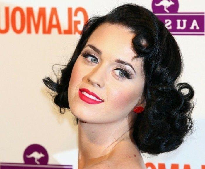 close up of katy perry, short curly retro styled hair, big fake lashes mascara and bold black eyeliner, vibrant red lipstick, blue eyes lip shaped stud earrings