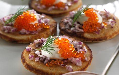 Imponer dine gæster ved at servere dekorative, portionsanrettede blinis med toppings som stenbiderrogn, ørredrogn eller røget laks.