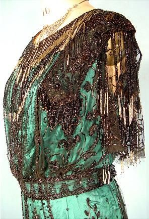 c. 1907 McGrath, San Francisco Green Silk Satin and Black Beaded Net Evening Gown. The gown has the monobosom bodice draped over boned understructure. The bodice has short net sleeves dripping with long silver and black bead fringe at neckline. The skirt has rounded train, of black net sewn with sequins and bugle beads in stylized floral patterns with runched chiffon band at hem. Detaile front