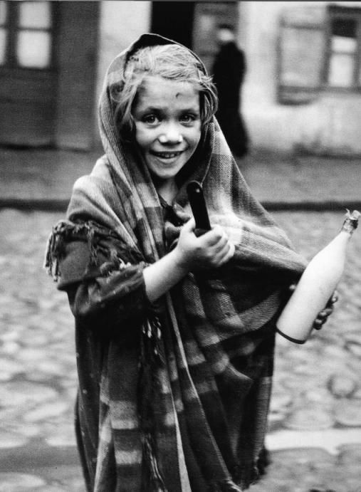 """Sehma è stata mandata in drogheria a cercare una pentola per la zuppa e una bottiglia di latte. Lodz, 1938. Suo padre era rientrato in casa sorridente. In tutta la giornata aveva trasportato carichi pesanti, percorso interminabili chilometri, ma ritornava con un po' di denaro, e la famiglia poteva permettersi un buon pasto. Io c'ero in quel giorno """"felice"""" e vidi che non ci voleva una gran cosa per procurare un po' di gioia."""